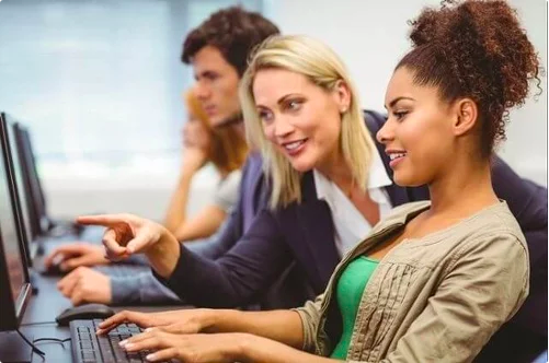 Woman pointing to female student's computer screen in class